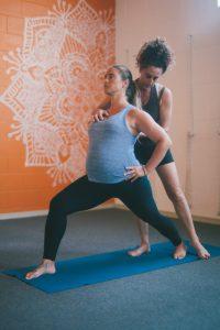 Vanessa Shribman helps pregnant woman get into yoga pose